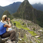 A tourist couple takes pictures of Inca's citadel of Machu Picchu in Cuzco December 2, 2010. Peru will celebrate on July 2011, the first centenary of the discovery of Machu Picchu with a huge exhibition after an agreement with Yale University to return thousands of artifacts taken from the archaeological site in the early 1900s, the Ministry of Culture said on Thursday. REUTERS/Enrique Castro-Mendivil (PERU - Tags: SOCIETY TRAVEL)